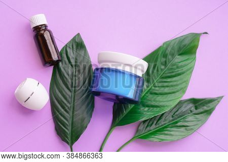 Top View Of Bottle Of Oil Essence, Jars And Containers With Cream Next To Green Natural Large Leaves