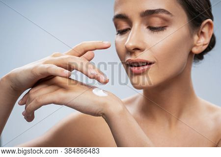 Young Woman Applying Body Care On Hand
