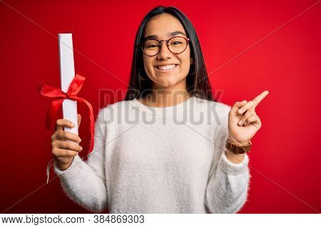 Young beautiful graduate asian woman holding university degree diploma over red background very happy pointing with hand and finger to the side
