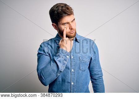 Young handsome blond man with beard and blue eyes wearing casual denim shirt Pointing to the eye watching you gesture, suspicious expression