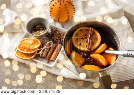 christmas and seasonal drinks concept - pot with hot mulled wine, orange slices, aromatic spices and ladle on grey background