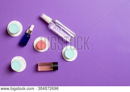Set Of Travel Size Cosmetic Bottles On Colored Background. Flat Lay Of Cream Jars. Top View Of Bodyc
