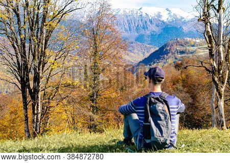 Alone Tourist Sits On The Edge Of A Cliff In The Autumn Forest, Looking At The Valley And Snowy Moun