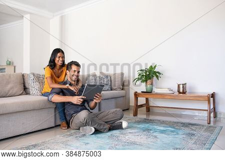Young middle eastern couple using digital tablet while sitting on couch and floor. Happy smiling indian woman embracing from behind her boyfriend while watching video on digital tablet at home.