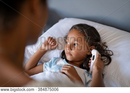 Close up of african mom using ear thermometer to check temperature of little sick girl lying on bed. Ill indian daughter with cold and flu symptoms resting in bed while mother checking fever.
