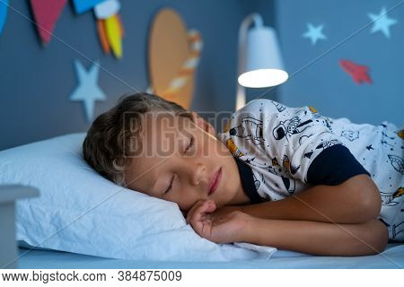 Cute little boy lying on side on bed and sleeping in bedroom decorated with planets and stars. Kid with closed eyes in his space themed room and dreaming of being an astronaut and going into the space