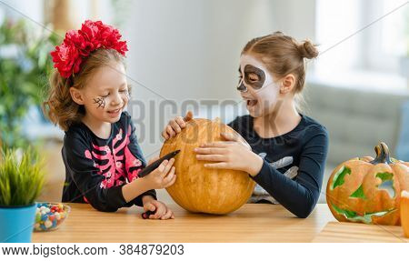 Happy family preparing for Halloween. Cute children in carnival costumes carving pumpkins at home.