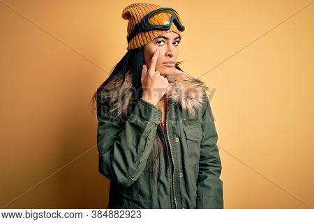 Young beautiful hispanic woman wearing ski glasses and coat for winter weather Pointing to the eye watching you gesture, suspicious expression