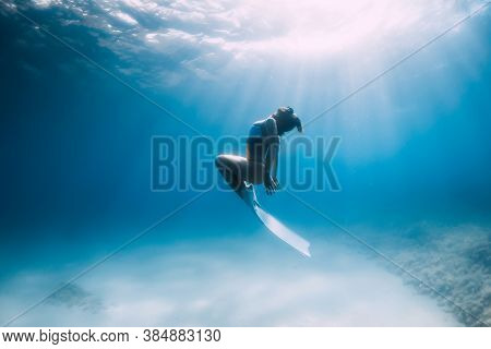 Freediver Glides Over Sandy Sea With White Fins. Attractive Woman Free Diver In Blue Ocean