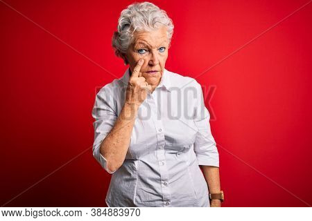 Senior beautiful woman wearing elegant shirt standing over isolated red background Pointing to the eye watching you gesture, suspicious expression