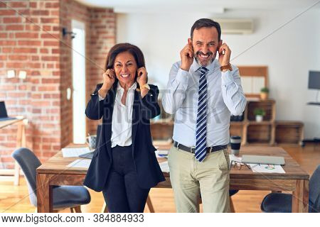 Two middle age business workers standing working together in a meeting at the office covering ears with fingers with annoyed expression for the noise of loud music. Deaf concept.