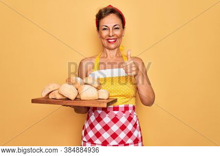 Middle age senior pin up housewife woman wearing 50s style retro dress and apron cooking bread happy with big smile doing ok sign, thumb up with fingers, excellent sign