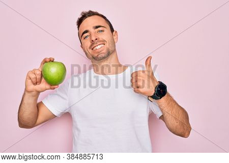 Young handsome man with blue eyes eating healthy green apple over isolated pink background happy with big smile doing ok sign, thumb up with fingers, excellent sign