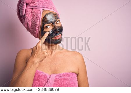 Middle age brunette woman wearing beauty black face mask over isolated pink background Pointing to the eye watching you gesture, suspicious expression