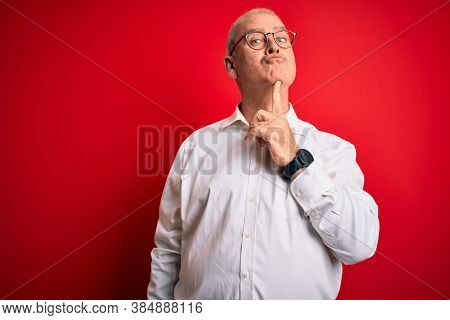 Middle age handsome hoary man wearing casual shirt and glasses over red background Thinking concentrated about doubt with finger on chin and looking up wondering