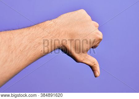 Hand of caucasian young man showing fingers over isolated purple background doing thumbs down rejection gesture, disapproval dislike and negative sign