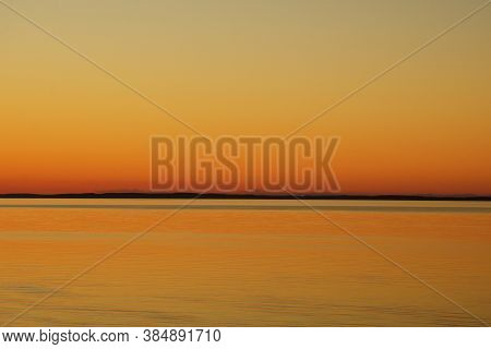 Clear Sky And Calm Lake Water With Light Ripples At Sunset