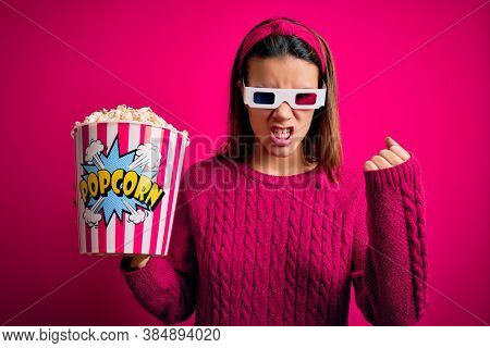 Young beautiful girl watching movie using 3d glasses eating box with popcorns angry and mad raising fist frustrated and furious while shouting with anger. Rage and aggressive concept.