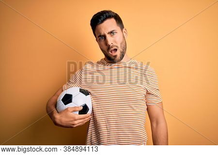 Handsome player man with beard playing soccer holding footballl ball over yellow background In shock face, looking skeptical and sarcastic, surprised with open mouth