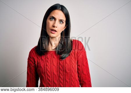 Young brunette woman with blue eyes wearing casual sweater over isolated white background In shock face, looking skeptical and sarcastic, surprised with open mouth