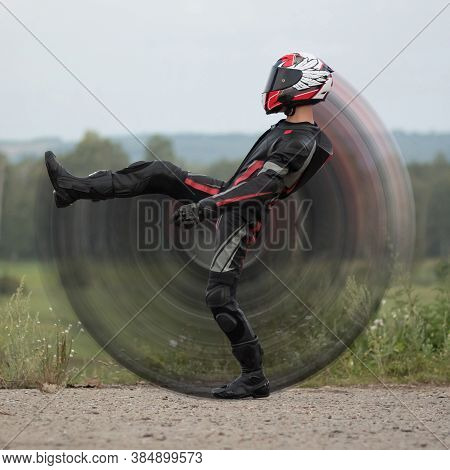 The Motorcyclist Swung His Leg. A Motorcyclist In Full Gear And A Helmet.