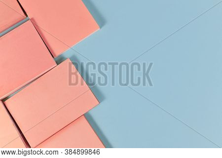 Small Blank Pink Paperback Books On Left Side Of Blue Background With Empty Copy Space
