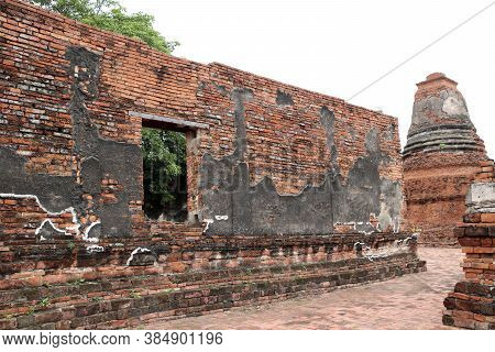 The Brick Wall With Window Of Church And Small Stupa In The Ruins Of Ancient Remains At Wat Worachet