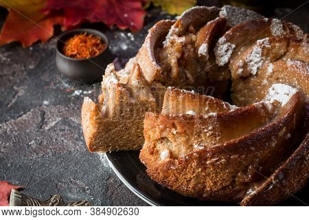Bundt Cake With Saffron And Rum Covered With White Glaze On Rustic Background With Autumn Decoration