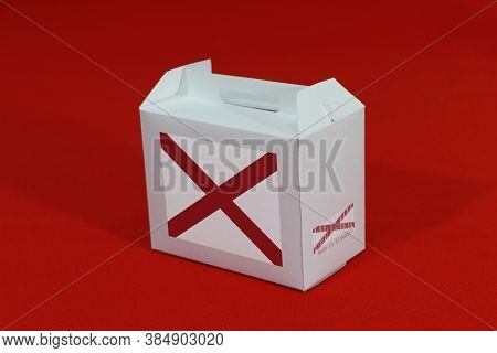 Alabama Flag On White Box With Barcode And The Color Of State Flag On Red Background. The Concept Of