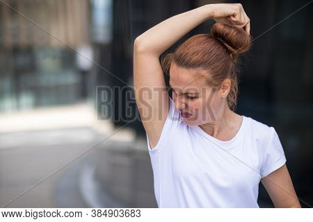 Sweaty Girl Sniffs Her Armpits In Disgust In White T-shirt. Young Woman Wrinkling Her Face Because O