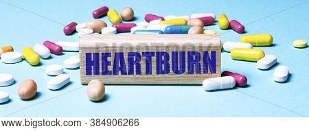 The Word Heartburn Is Written On A Block Of Wood On A Light Blue Background Among Multi-colored Pill