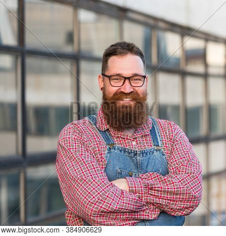 Brutal Bearded Manual Worker In Eyeglasses Wearing Blue Overalls, Checked Shirt In Vintage Style, Lo