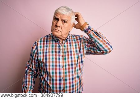 Senior handsome hoary man wearing casual colorful shirt over isolated pink background confuse and wondering about question. Uncertain with doubt, thinking with hand on head. Pensive concept.