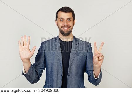 Young Businessman Man With Beard Smiling, Showing Number Seven With Fingers On Hand, Smiling Confide