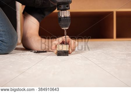 A Man Drills A Hole In The Wood Against The Background Of An Inverted Closet On The Floor.