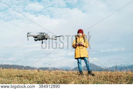 Close Up Image Of Flying Drone With Teenager Boy Dressed Yellow Jacket On Background Piloting A Mode