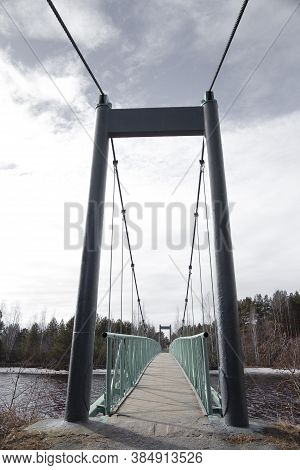Newly Painted, Old Cable-stayed Bridge Over A Small River