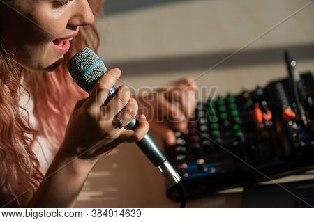 A Woman Sings A Song Into A Microphone And Records Her Singing.