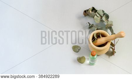 Dry Eucalyptus Leaves, Natural Essence And Wooden Mortar And Pestle On The Green Blue Background. Al