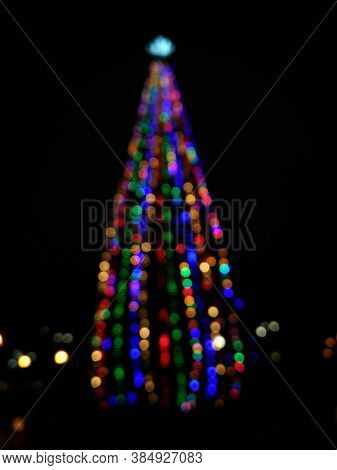Christmas Tree In Defocus Shooting At Night In A City Park, Bokex Reflexes, Blurred Image For Backgr