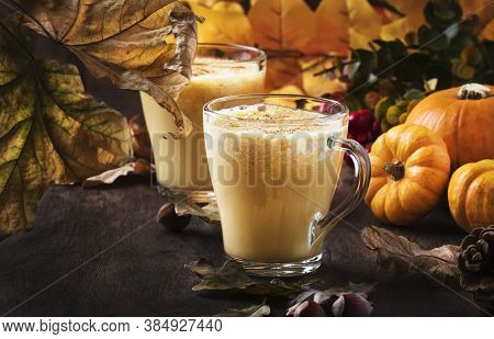 Pumpkin Spiced Latte Or Coffee In Glass Cup On Vintage Wooden Table. Autumn Or Winter Hot Drink