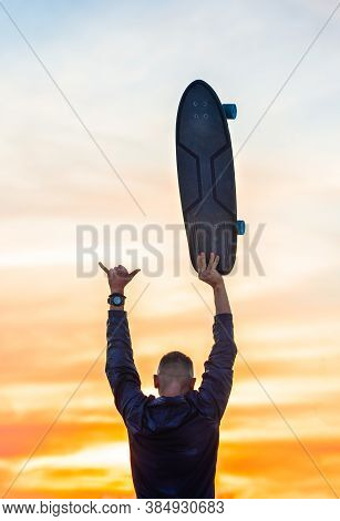 Carefree And Relaxed Skater Enjoying Life On Sunset Or Sunrise. Holds Surf Skateboard In Right Hand