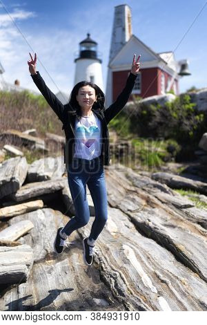 A Happy Chinese Woman Jumoing Above The Rocks At  Pemaquid Point Lighthouse Park In Bristol Maine On