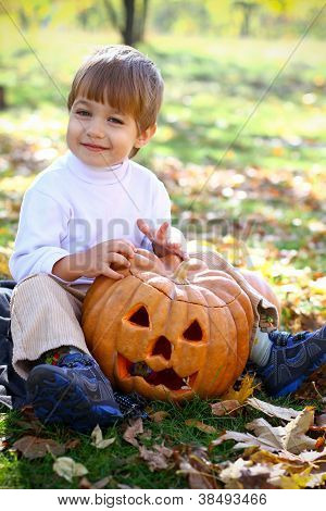 Portrait Of A Happy Little Boy With Halloween Pumpkin Who Sitting On The Grass