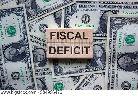 Concept Words 'fiscal Deficit' On Wooden Blocks On A Beautiful Background From Dollar Bills. Busines