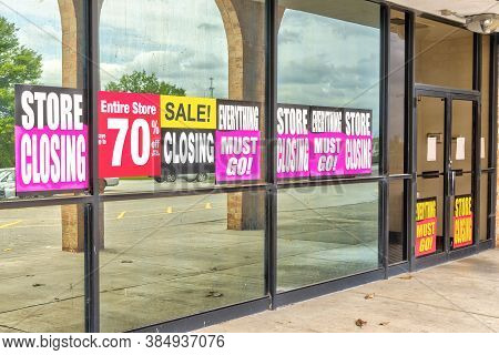 Horizontal Shot Of Going Out Of Business Signs In A Retail Store's Windows.