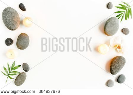 Spa Stones, Palm Leaves, Flower White Orchid, Candle And Zen Like Grey Stones On White Background. F