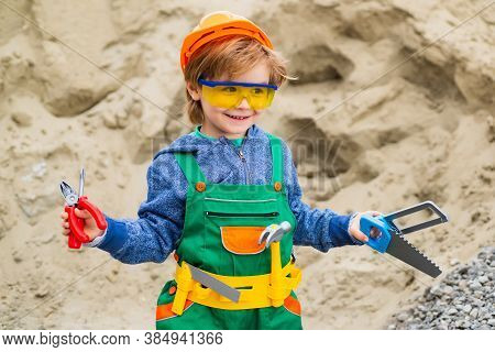 Cute Little Boy In Yellow Hard Hat And Toy Tools. Safety Glasses For Engineer. Little Builder.