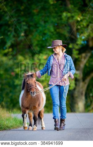 Girl in Western clothing is walking with a horse outdoor. Young woman leads a Shetland pony along the road in summertime.