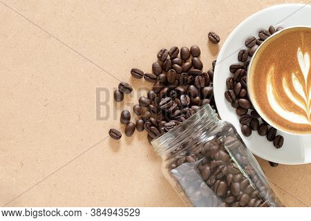 Roasted Coffee Beans In A Glass Jar And Latte Art On Cappuccino Coffee Cup Over Craft Board.